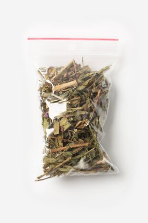 Plastic transparent zipper bag with full of blooming Sally tea isolated on white, Vacuum package mockup with red clip. Concept.