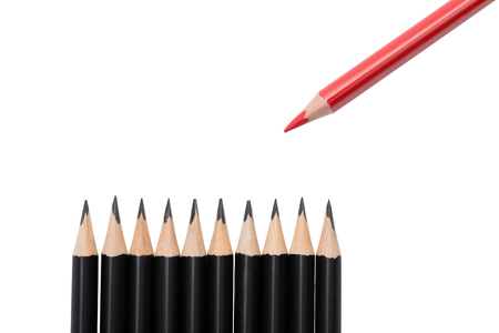 Red pencil among black ones on white background. A set of stationery pencils for drawing with one red pencil to underline the main element in the drawing. Pencils Isolated on white background