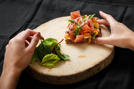 Close up sandwich with jamon and salad on board. Womans hand holding folk and knife. Sandwich with jamon and apple, salad. Delicious lunch. Serving dishes concept. Restaurant food concept Foto de archivo