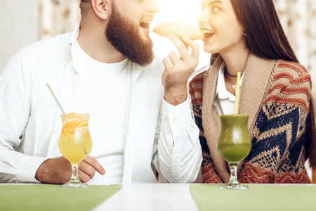 Portrait of a happy young couple in a restaurant. A happy couple in love with a man and a woman eat a croissant one for two. Romantic date in a restaurant with delicious alcoholic cocktails
