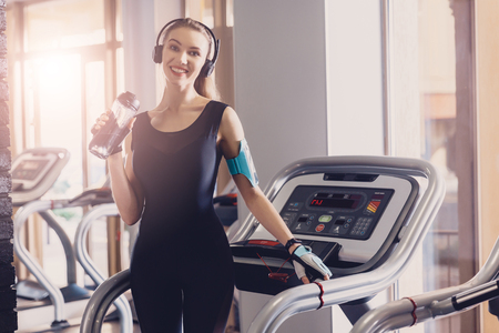 The girl after a workout on a treadmill is resting. After jogging on the treadmill, the girl takes a breath and restores strength with a sip of water to quench thirst. Sportswear for sports.