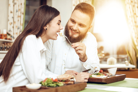 Romantic dinner happy men and women in restaurant. Happy couple enjoying a romantic dinner in two. A wonderful romantic evening of young guys in the restaurant. The concept of festive mood