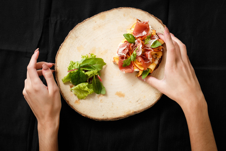 Top view sandwich with jamon and salad on board. Womans hand holding folk and knife. Sandwich with jamon and apple, salad. Delicious lunch. Serving dishes concept. Restaurant food concept