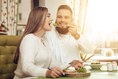 Happy man and woman have lunch in a restaurant. A smiling couple man and women enjoy their romantic lunch in a restaurant. Guy feeds a girl salad. The concept of the restaurant business. Imagens