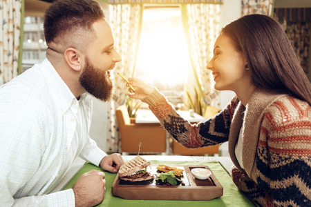 Happy man and woman are having lunch in a restaurant. Smiling man and woman couple enjoying their romantic lunch. Girl feeds the guy with a sandwich. The concept of the restaurant business. Archivio Fotografico