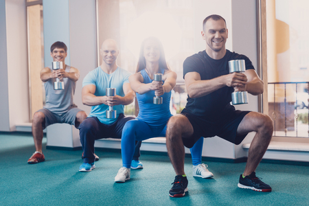 People performs physical exercise with dumbbells. A group of men and women performs squats with dumbbells. Strength training with dumbbells to improve the fitness of people. Sports equipment 免版税图像