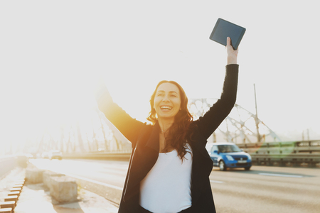 Young smiling girl rejoices holding her hands up. A beautiful young girl joyfully raised her hands up from the received letter on the tablet. Girl at dawn stands on the bridge. Happy man concept