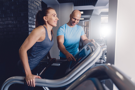 Personal training with a trainer on a treadmill. The trainer controls the correctness of the exercise when using a treadmill for cardio. Control coach in the gym. Athletic jogging with a trainer