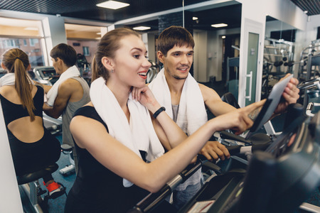 A man and a woman are watching a training video. A group of two young people watching a video about exercise on a tablet. Woman resting after workout sitting on the sports equipment in the gym Stock Photo