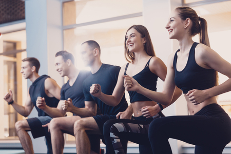Group men and women performs a physical exercise. Joint exercise of men and women. Exercise to improve shape in a sport hall. Happy mens and womens sportswear for training in the gym.
