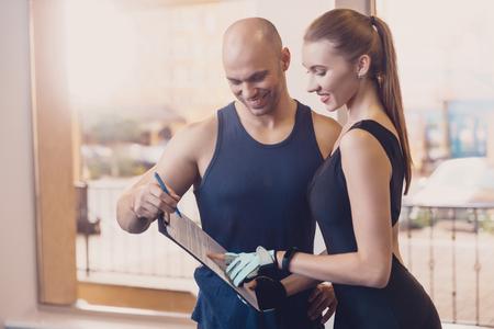 L'entraîneur rédige un programme de remise en forme qui entraîne la fille. Le programme d'entraînement physique pour des résultats efficaces lorsque vous travaillez en salle. Travail sur le travail physique avec un entraîneur individuel dans un club de fitness.