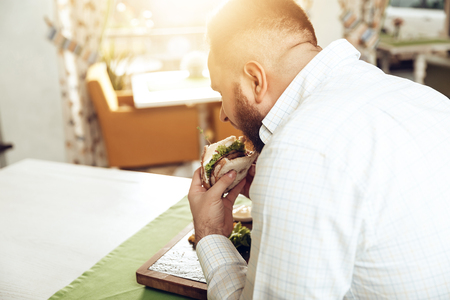 Back view man bite sandwich eating in cafe. A happy bearded man rejoices in a restaurant, consuming his food, which he ordered. The concept of restaurant business and service.