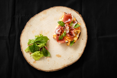 Sandwich with jamon and lettuce on a wooden tray. Top view of grilled jamon sandwich for a quick snack with fresh lettuce. The concept of fast food in the restaurant. Foto de archivo