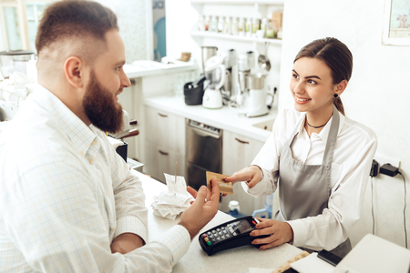 Cheerful cashier using digital device for payment. A smiling girl waiter calculates a bearded man in a cafe with a bank card. The concept of the restaurant business and service maintenance Imagens