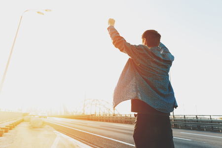 Glücklicher Mann steht mit erhobenen Armen. Glücklicher Mann, der mit seinen Händen vor Freude springt. Glücklicher junger Mann bei Sonnenaufgang auf Autos einer geschäftigen Brücke. Das Konzept einer freien und fröhlichen Person Standard-Bild