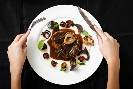 Top view of meat dish with grilled vegetables. Female hands holding cutlery. Grilled beef with vegetables and grilled engraving. The concept of serving dishes. Food concept for restaurants.