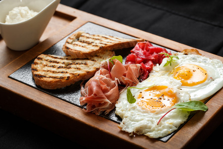 Close up breakfast eggs and toast jamon and cheese. American breakfast concept. Food on wooden board. Delicious lunch. Serving dishes concept. Restaurant food concept, healthy food.