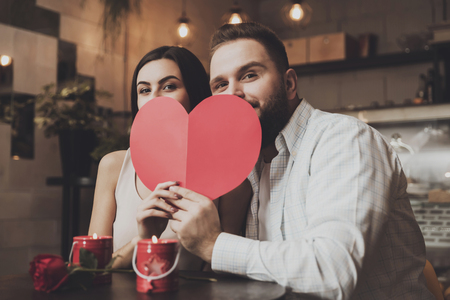 Young charming couple hides behind paper heart. Romantic meeting in the cafe of lovers men and women. Celebration of Valentine Day in a cafe for a romantic dinner together.