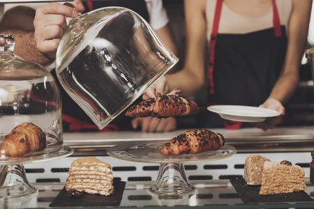 Una niña recibe un croissant del escaparate de una tienda. Hermosa chica prepara pasteles frescos para emitir un pedido de cliente en un café. El concepto de restaurante y servicio al cliente. De cerca