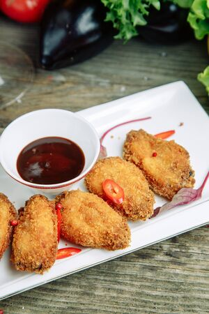 Restaurant dish on a wooden background with vegetables. Breaded chicken wings with sauce on a plate.