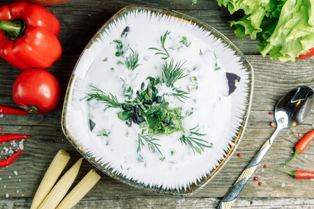 Restaurant dish on a wooden background with vegetables. Azerbaijani Dovga soup with greens on a plate. Stock Photo