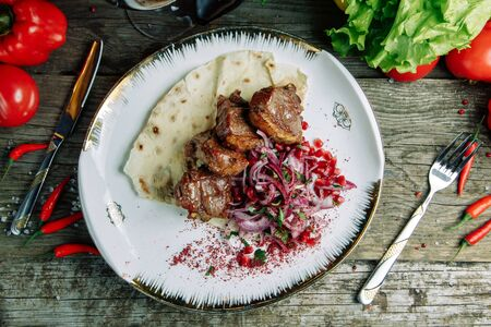 Restaurant dish on a wooden background. Azerbaijani shish kebab and grilled ribs.