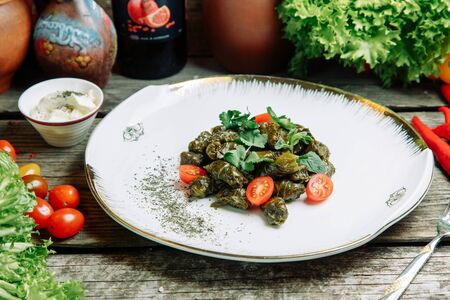 Azerbaijani restaurant dish with vegetable decor. At home on a plate with sauce and herbs.