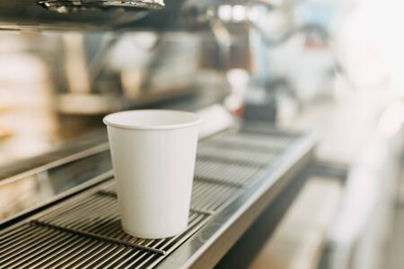 A cardboard Cup for coffee with you. White coffee Cup in the coffee machine.