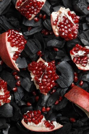 Red fruit slices on a dark texture. Preparation for hookah. Ripe cut pomegranate. Black charcoal background.