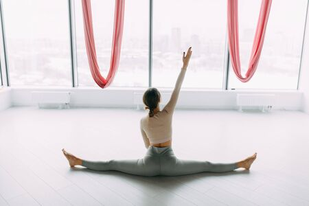 Stretching exercises on the floor and in the air. Beautiful girl athlete sitting on the twine. Room for a yoga workout with hammocks. Imagens