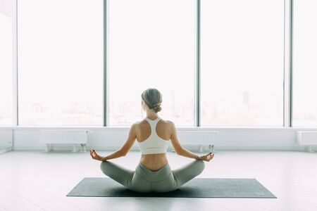 Exercises for self-control in yoga. White Windows with a panorama of the city. Relaxed posture during meditation. The girl is sitting on the Mat, relax.