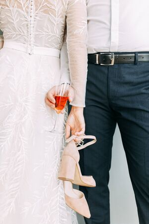 Intimate parts of the body, the atmosphere of the occasion. Wedding shoes, dress details and hands.