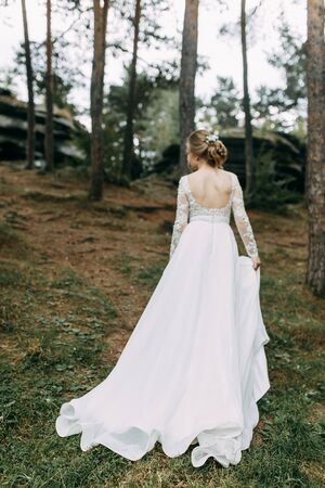Elegant ceremony in European style. Beautiful bride in white flying dress in the forest. Archivio Fotografico