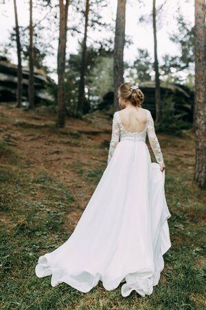 Cérémonie élégante dans un style européen. Belle mariée en robe volante blanche dans la forêt. Banque d'images