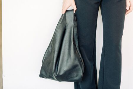 Women's leather bag in the hands of a stylish girl. Weblog survey for storefront and social networking.