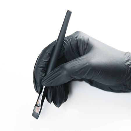 The girl's hand in a black glove. Cut out the white background, isolated. Brushes for eyebrow and makeup artist. Imagens