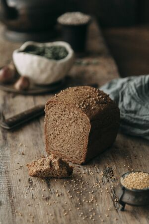 Fresh rye and grain bread on dark wooden background. Food styling and cooking with fresh ingredients. Archivio Fotografico