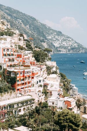 The coast of Positano, Amalfi in Italy. Panorama of the evening city and the streets with shops and cafes. Houses by the sea and the beach. Ancient architecture and temples. View from a postcard on top Banco de Imagens