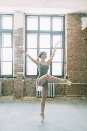 A young ballerina is getting ready, stretched and dancing. Poses in ballet. Photo shoot in the loft Studio. Russian Ballerina at the bench. ballet flats and dance dress