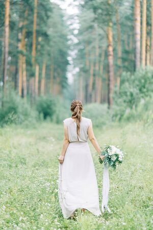 Boudoir photo shoot of the bride in the woods with a bouquet. Flying dress and beautiful girl in the Park. Archivio Fotografico