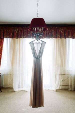 Wedding dress hanging on the chandelier in the hotel. Details on the dress, embroidery and boudoir photo. Banco de Imagens