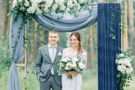 Wedding ceremony at the arch with pine forest in the style of fine art. Beautiful couple and traditions at a wedding in Europe.