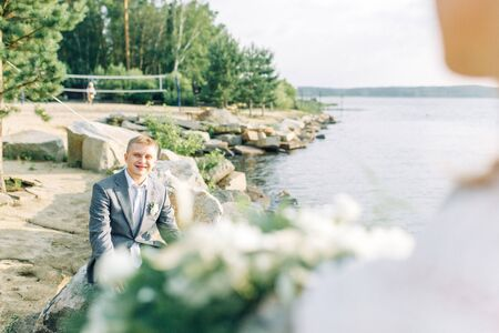 Groom in nature by the water. Gathering of a young man on the pier at sunset.
