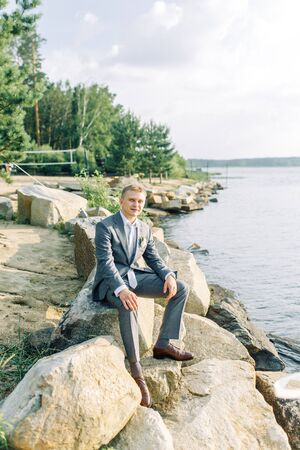 Groom in nature by the water. Gathering of a young man on the pier at sunset. Foto de archivo - 150168740
