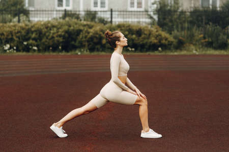 A sporty woman trains and exercises at a fitness stadium. Warm-up in the open air, stretching.