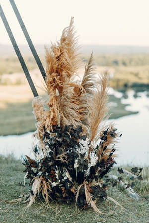 Wedding triangular arch in boho style. Floristics from dried flowers for a wedding, exit ceremony.