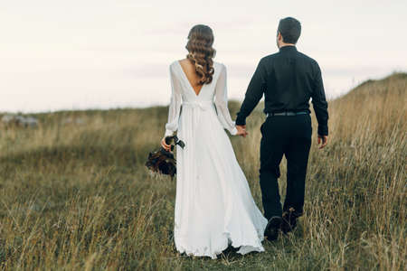 A beautiful fairy-tale happy bride with a bouquet and a wreath and a stylish groom on the background of rocks in the mountains. Boho wedding in nature. Standard-Bild