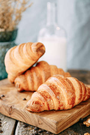 Breakfast with croissants and milk close-up. Freshly baked croissants on a wooden table.