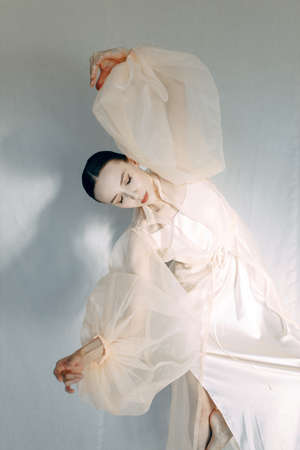 A beautiful girl poses in the studio, in the style of fine art. Fashion art photo of a young sensual lady in a flying dress.