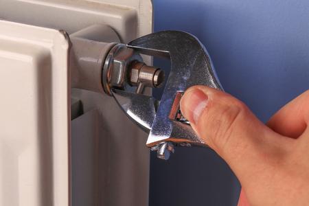 Hand eines Mannes, Mechaniker, Installation Reparatur Heizkörperventil Nahaufnahme Standard-Bild